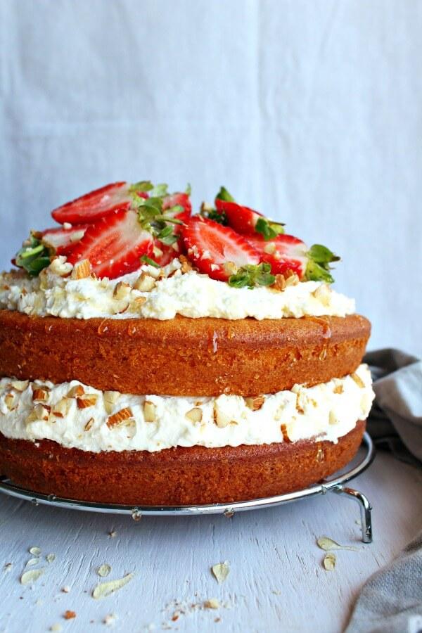 Zesty Orange Honey Layer Cake. The moistest, most tasty orange sponge cake with whipped cream & chopped almond layers & fresh strawberries on top. AMAZING!   berrysweetlife.com